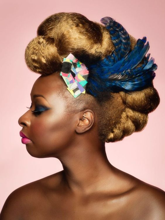 updo hairstyle on natural hair, fauxhawk with feathers
