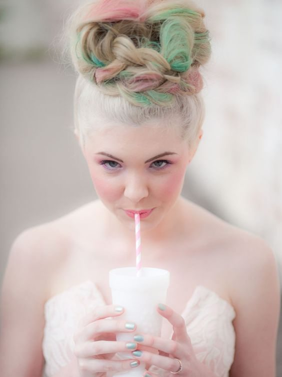 braided updo hairstyle with pink and green highlights