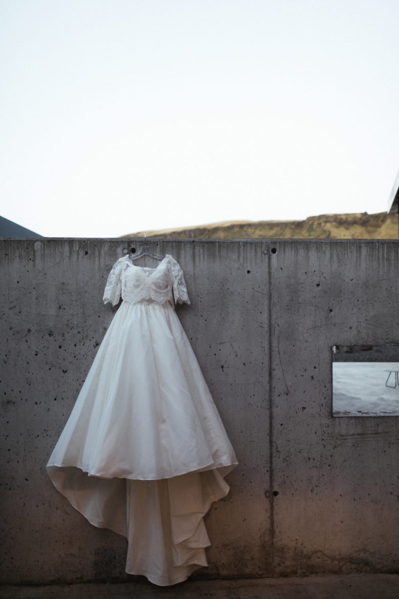 Wedding dress hanging on cement wall
