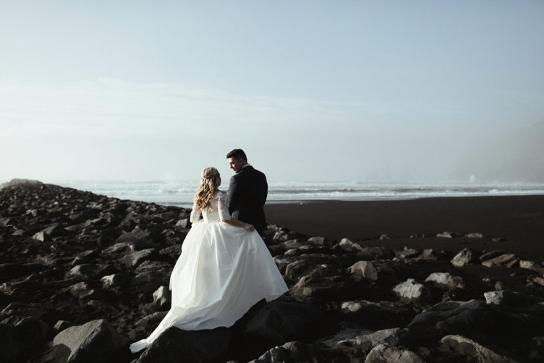 Bride and groom on rocks near ocean