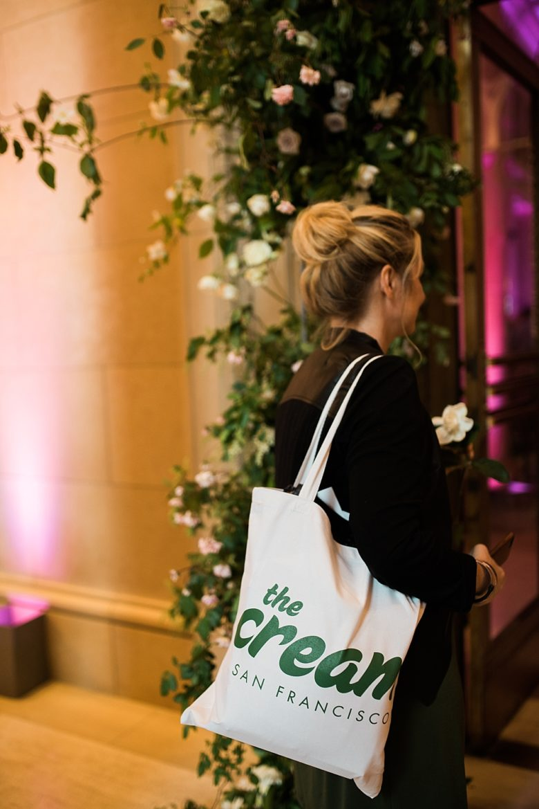 a woman walking into the cream event with a gift bag