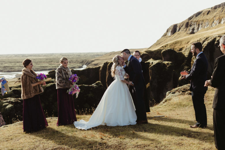 Bride and groom kissing in wedding ceremony in Fjaðrárgljúfur