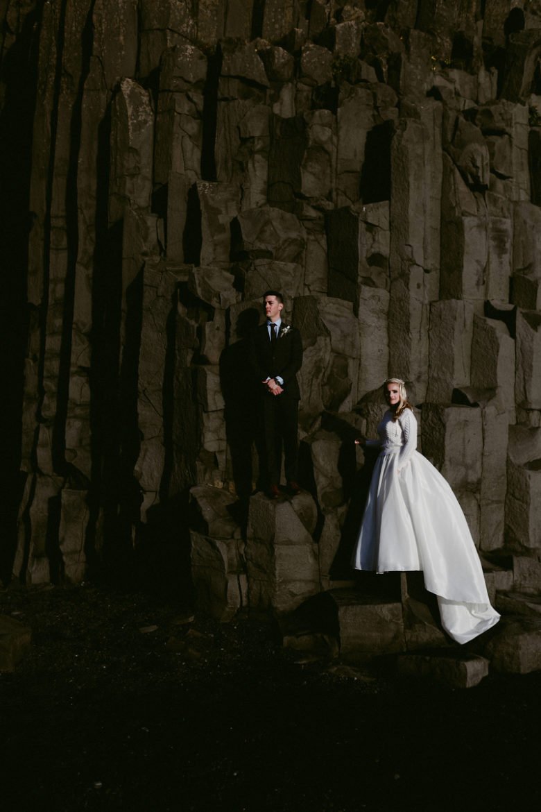 Bride and groom in front of rocky cliff in Fjaðrárgljúfur