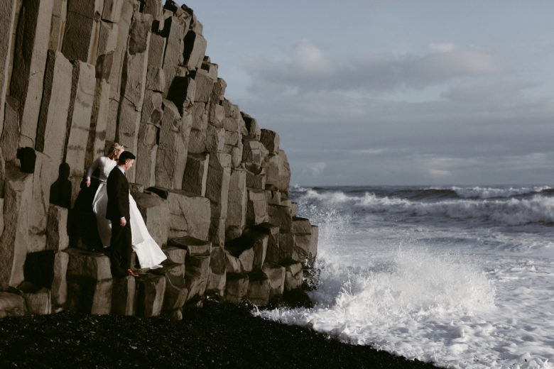Bride and groom near rocky cliff and ocean