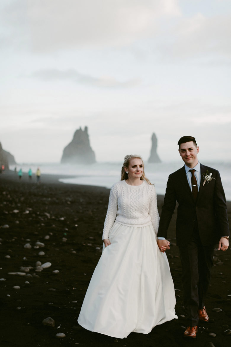 Bride wearing white cable-knit sweater, with groom in Fjaðrárgljúfur