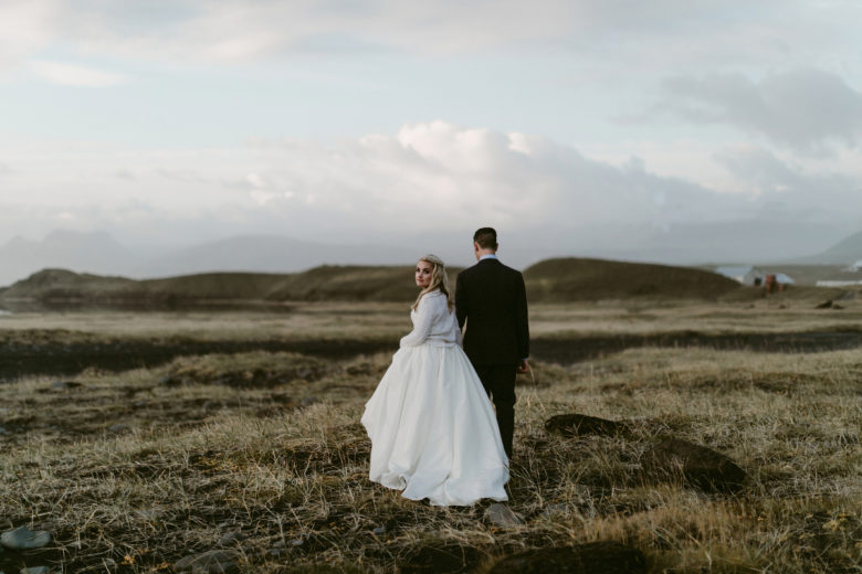 Bride and groom in field in Fjaðrárgljúfur