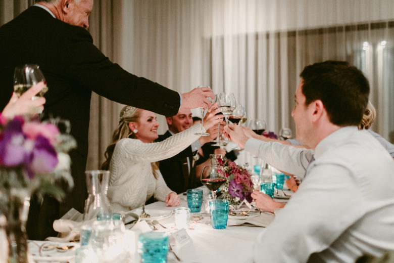 Bride, groom, and guests toasting at wedding dinner reception