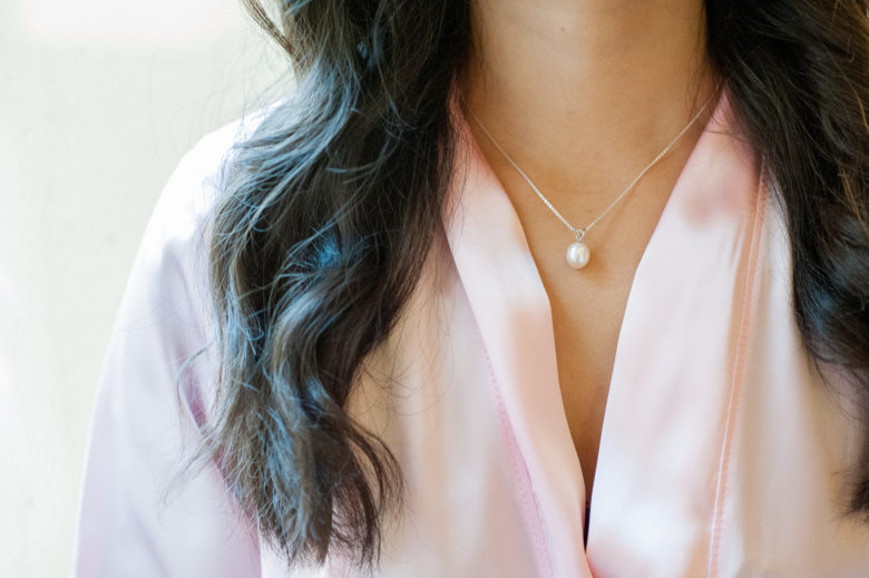 Close up of woman's neck and torso, wearing a pink robe and necklace with pearl
