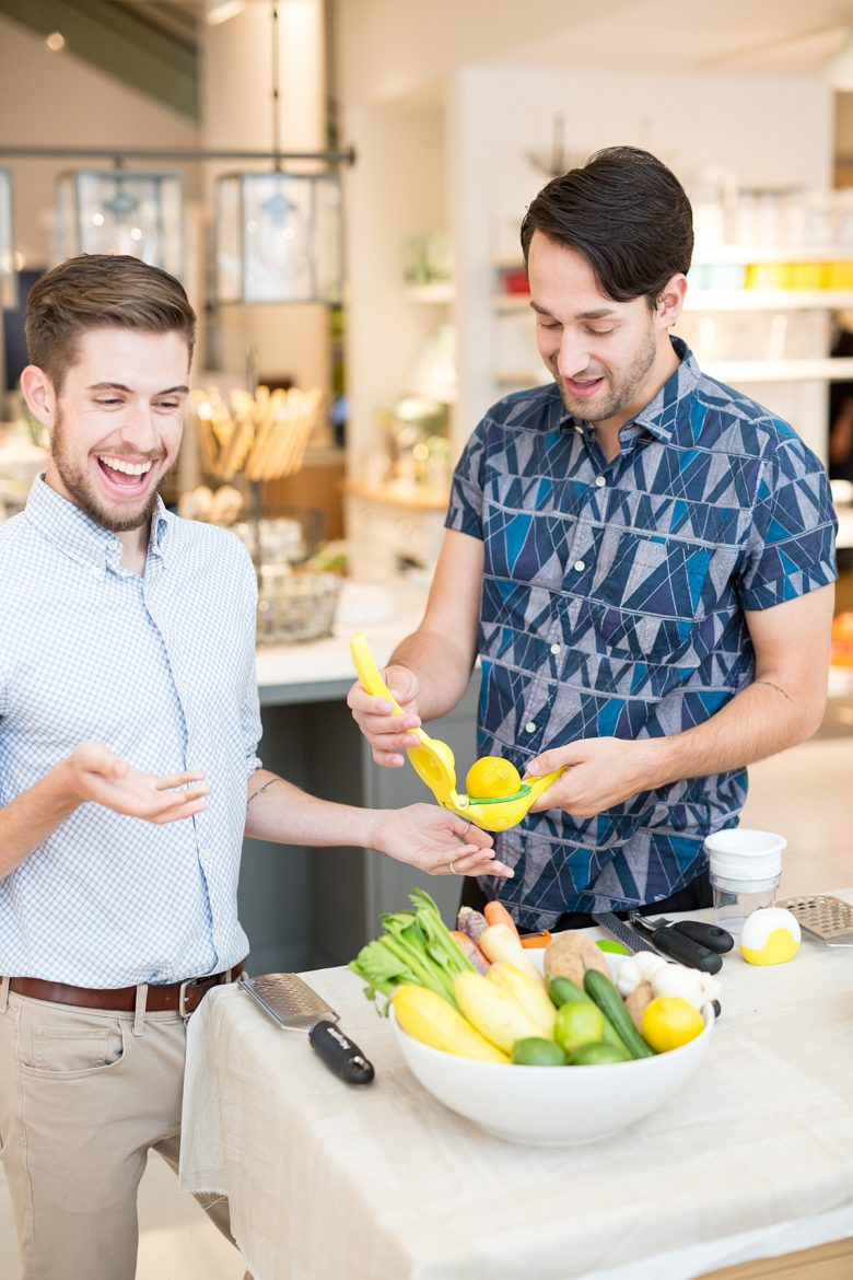 Author and his partner testing out kitchen tools with a bowl of fruits and vegetables at Crate and Barrel