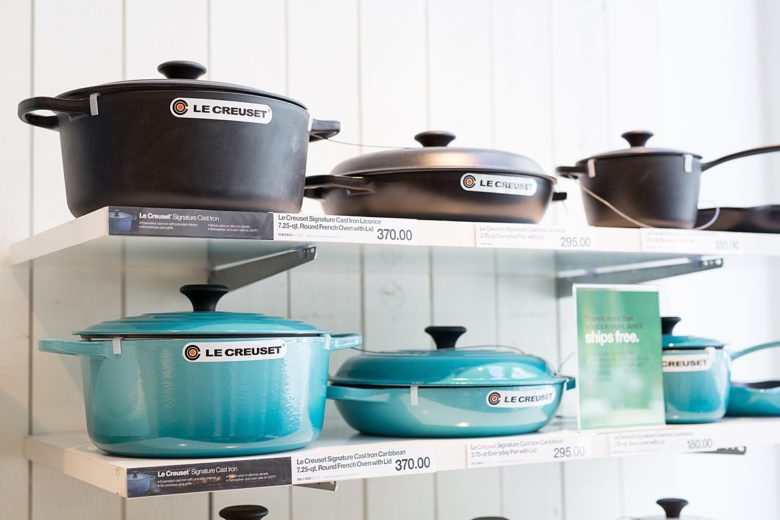 Crate and Barrel shelves holding Le Creuset Signature Round Ovens and Le Creuset Signature Everyday Pans