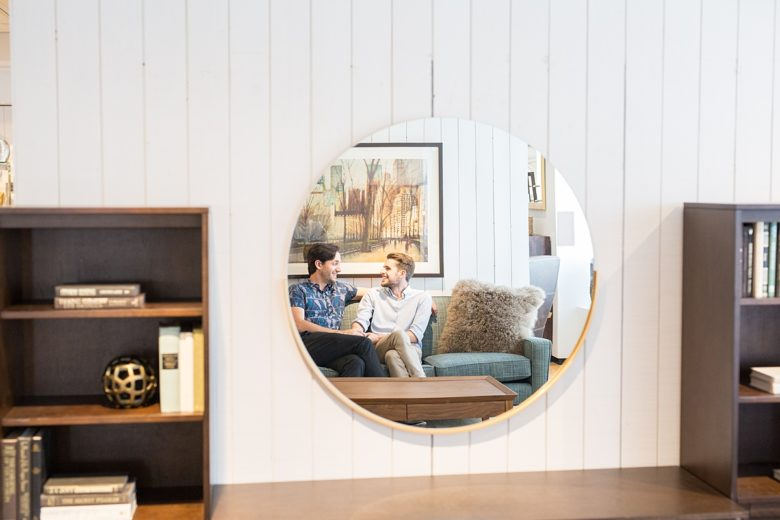 Author and his partner reflected in Gerald Round Wall Mirror above HD Media Console with Towers at Crate and Barrel