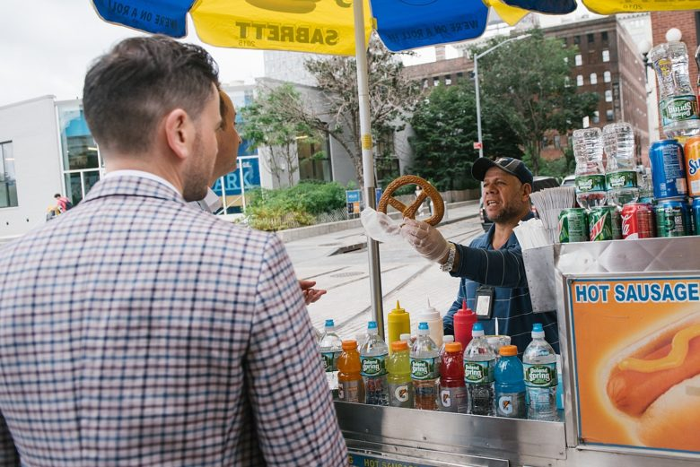 two grooms buying a pretzel from a street vendor