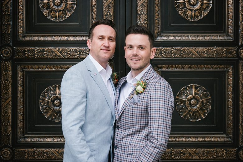 close up of two grooms in front of New York City Hall doors