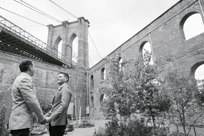 black and white portrait of two grooms at base of brooklyn bridge