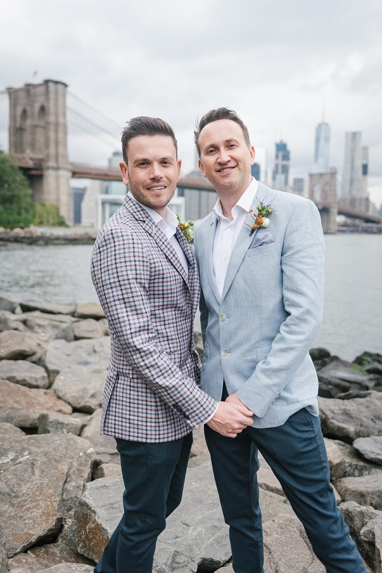 portrait of two grooms in front of Brooklyn Bridge and Manhattan skyline