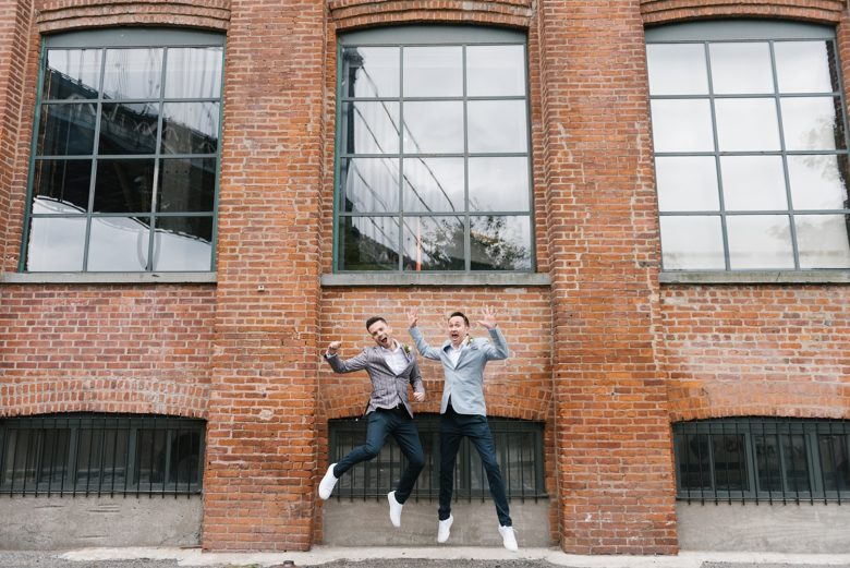 two grooms jumping for joy in front of brick industrial building