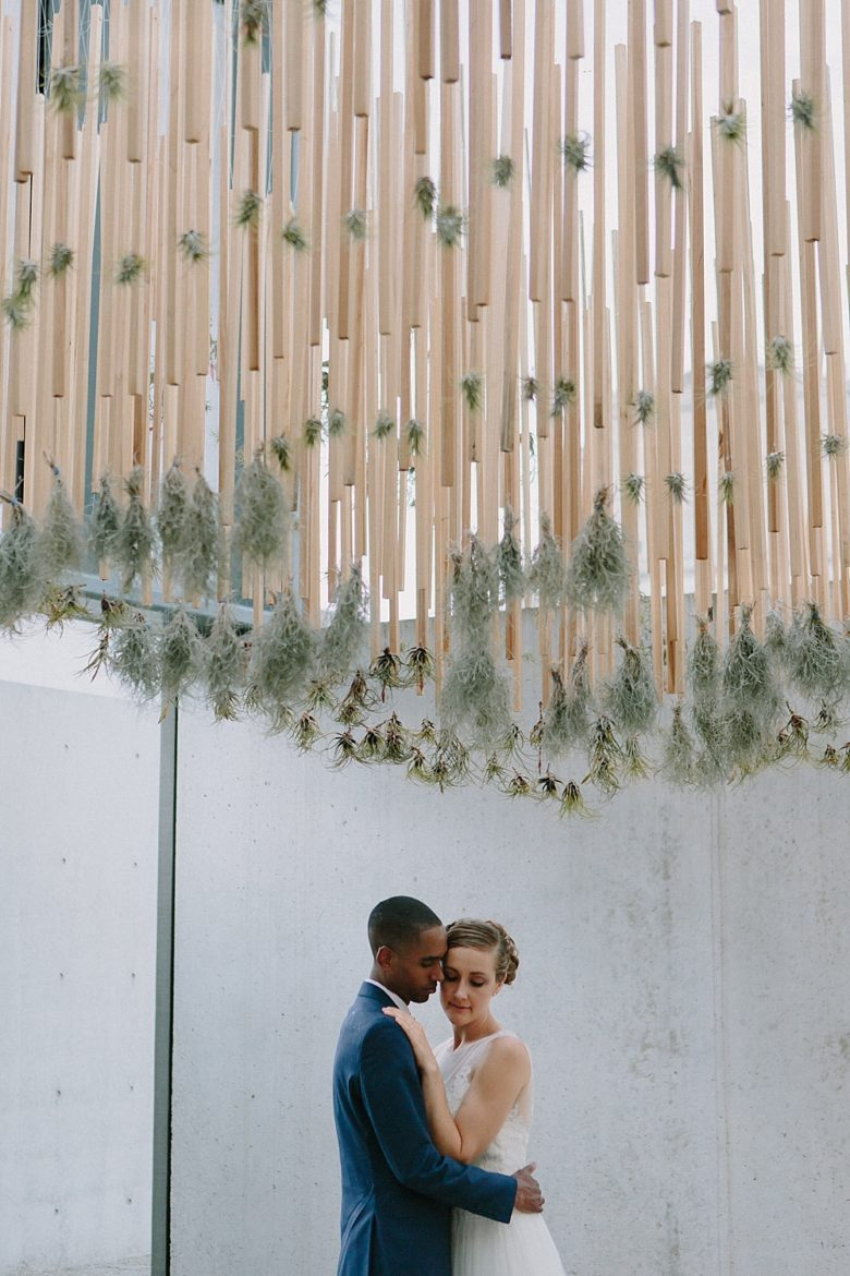 Bride and groom portrait in front of wood, air plants, and concrete