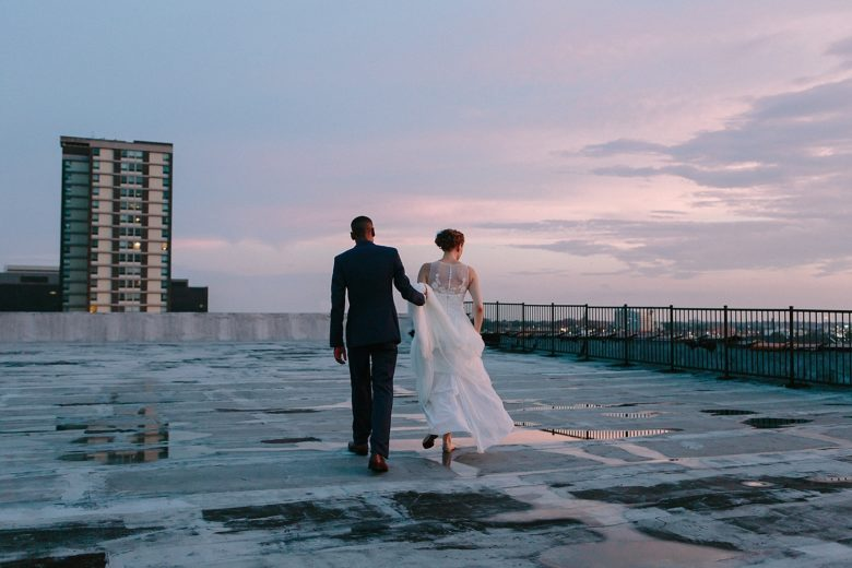 Bride and groom on roof at sunset