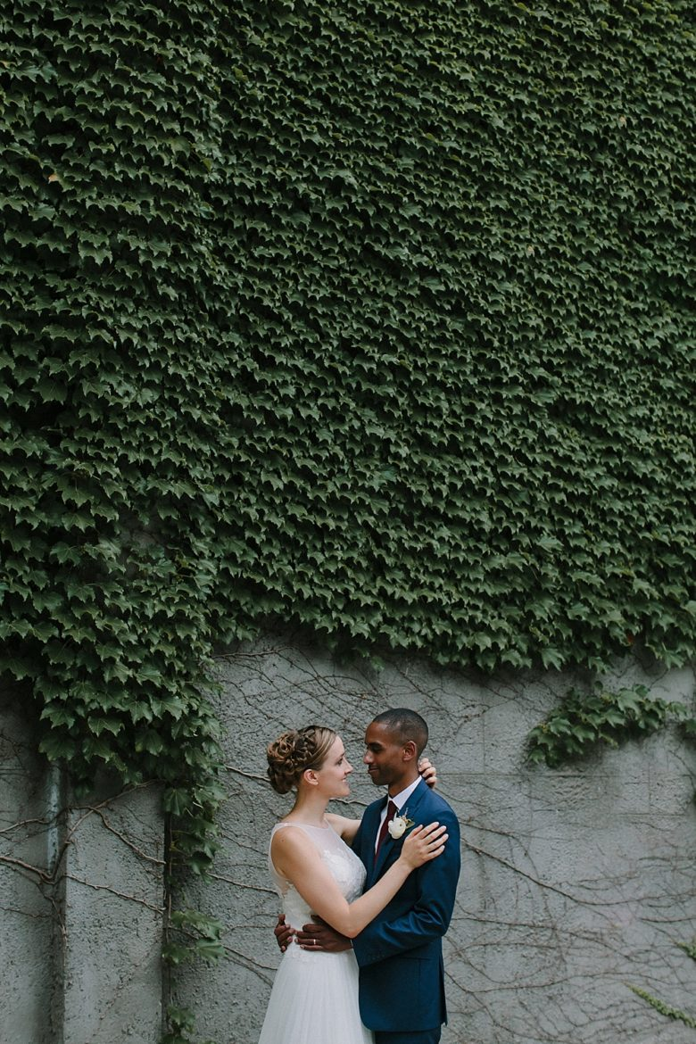 Bride and groom portrait in front of ivy-covered wall