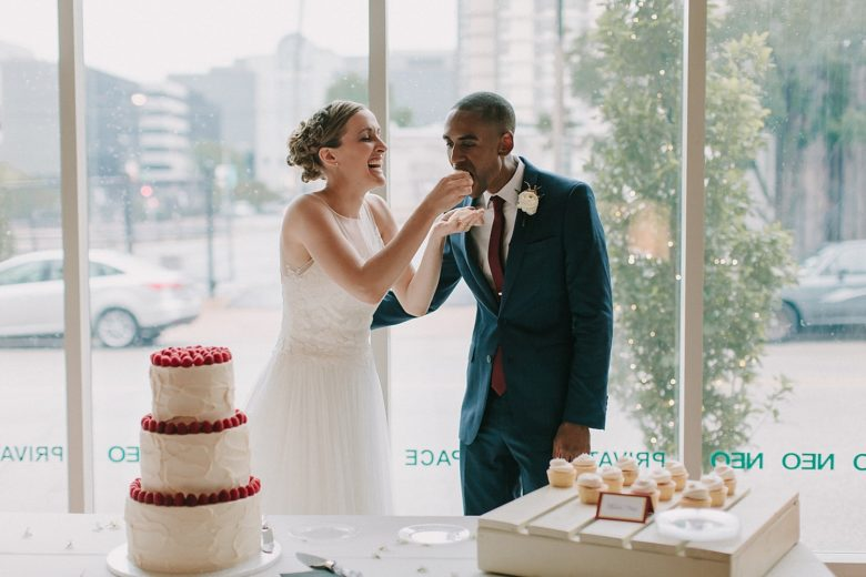 Bride feeding groom first cupcake