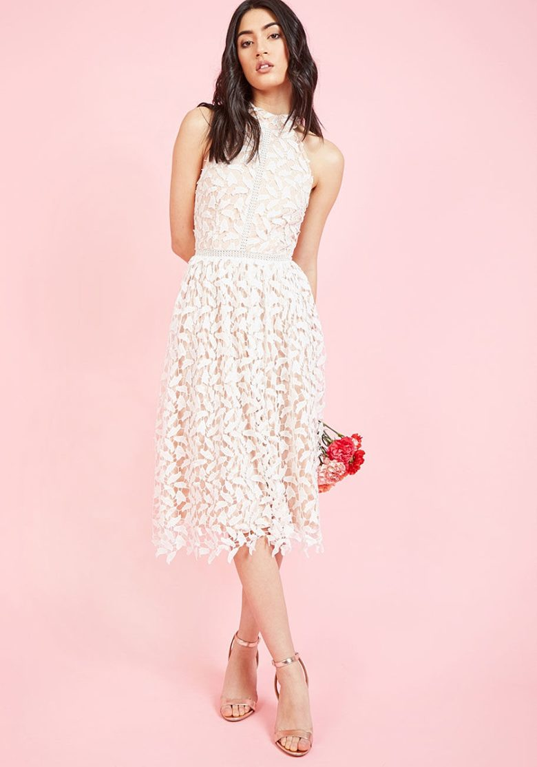 woman in sleeveless lace bridal shower dress on pink background