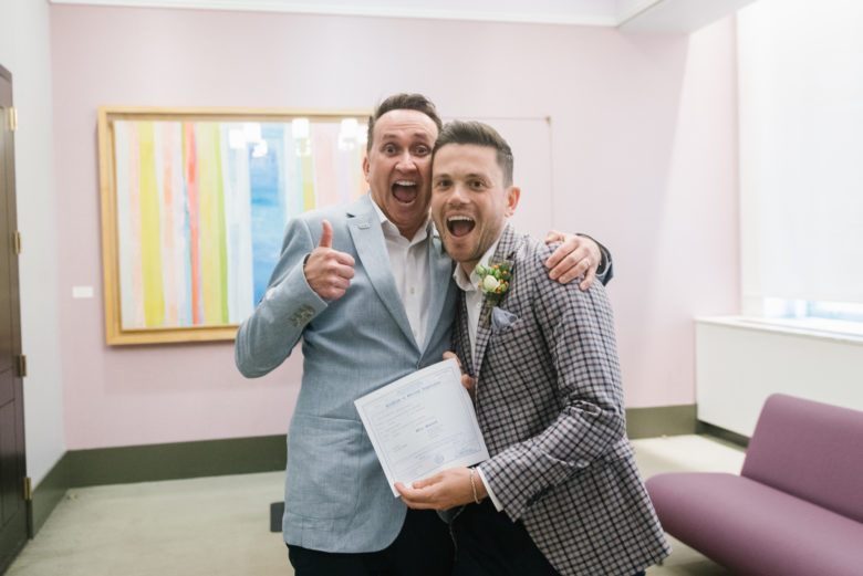 two grooms in New York City Hall with marriage certificate